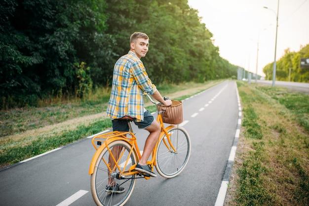 Junger glücklicher mann auf gelbem weinlesetrad mit korb, grüner sommerpark. radfahren im freien. männliche person auf retro-fahrrad