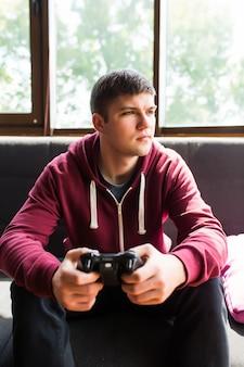 Junger glücklicher mann, der am wochenende lacht und videospiele spielt