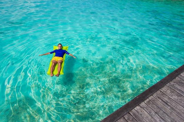 Junger glücklicher mann, der auf aufblasbarer matratze im meer sich entspannt
