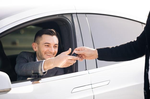 Junger glücklicher mann, der autoschlüssel zu ihrem neuen automobil empfängt