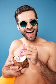 Junger glücklicher mann, der cocktail von kokosnuss hält