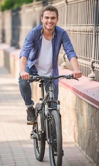 Junger glücklicher mann, der fahrrad nahe dem stadtpark fährt.