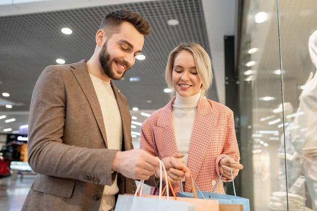 Junger glücklicher mann, der in einkaufstaschen schaut und mit seinem einkaufen mit stylistin glücklich ist