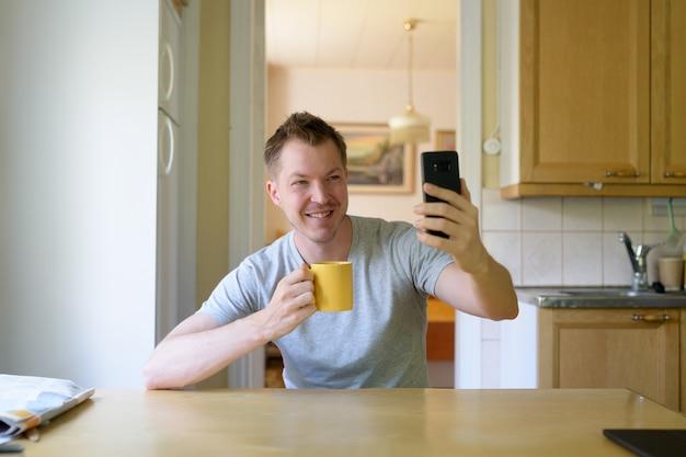 Junger glücklicher mann, der selfie beim kaffeetrinken durch den windo nimmt