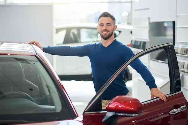 Junger glücklicher mann, der sich auf auto im autohaus stützt.