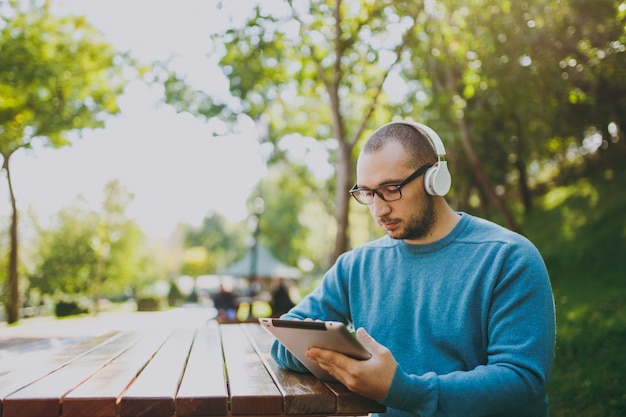 Junger glücklicher mann, geschäftsmann oder student in lässigen blauen hemdgläsern, die mit kopfhörern am tisch sitzen, tablet-pc im stadtpark, musik hören, draußen auf grüner natur ausruhen. lifestyle-freizeitkonzept.