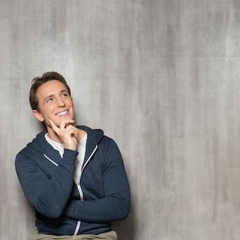 Junger glücklicher mann im blauen sweatshirt-denken