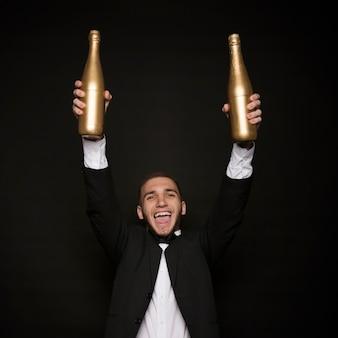 Junger glücklicher mann in der abendessenjacke mit flaschen des getränks