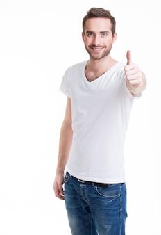 Junger glücklicher mann mit daumen hoch zeichen in casuals lokalisiert auf weißem hintergrund.