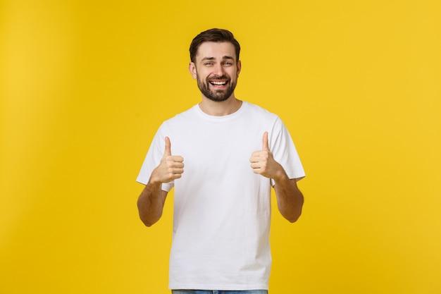 Junger glücklicher mann mit den daumen oben unterzeichnen herein die zufälligen, die auf gelb lokalisiert werden