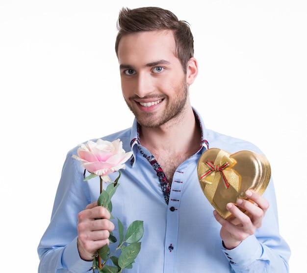 Junger glücklicher mann mit einer rosa rose und einem geschenk - lokalisiert auf weiß.