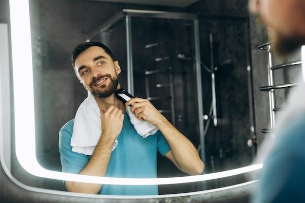 Junger glücklicher mann mit handtuch, der auf den spiegel schaut und sich früh morgens im badezimmer rasiert