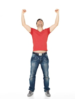 Junger glücklicher mann mit in lässigen mit erhabenen händen oben isoliert auf weiß