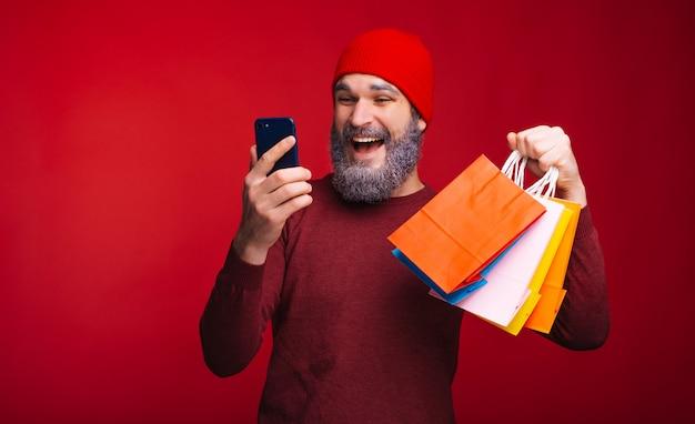 Junger glücklicher mann mit weißem bart, der online-einkauf macht und einige papiereinkaufstaschen hält
