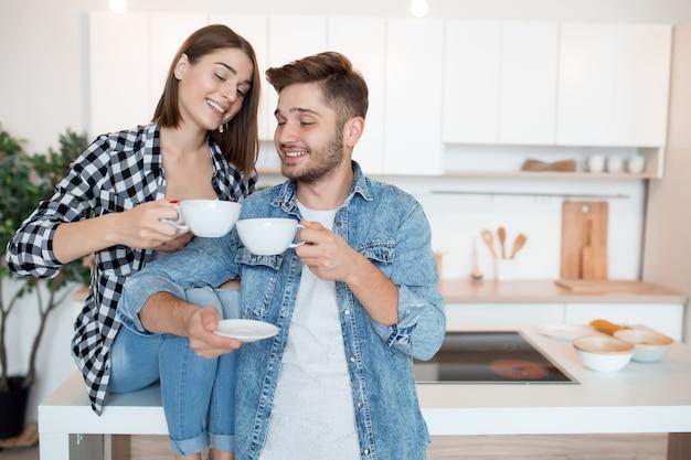 Junger glücklicher mann und frau in der küche, frühstück, paar zusammen am morgen, lächelnd, tee trinkend