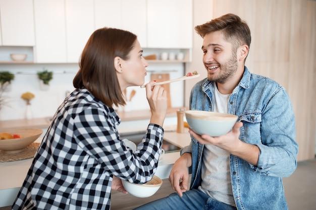 Junger glücklicher mann und frau in der küche, frühstückend, paar zusammen am morgen, lächelnd