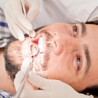 Junger glücklicher mann und frau in einer zahnärztlichen untersuchung am zahnarzt