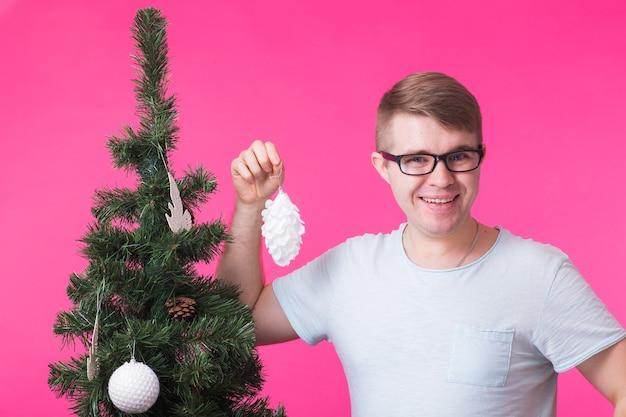 Junger glücklicher mann zeigen weihnachtsdekorationen