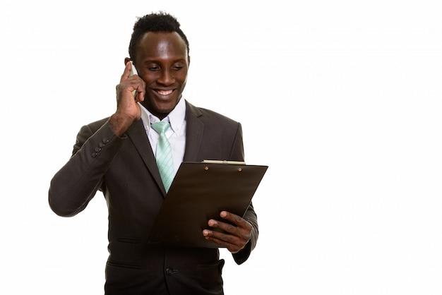 Junger glücklicher schwarzafrikanischer geschäftsmann, der lächelt, während am telefon spricht