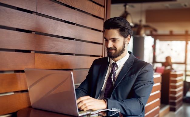 Junger glücklicher stilvoller bärtiger geschäftsmann im anzug, der in einem café mit musik und laptop nach der arbeit neben der holzwand entspannt.