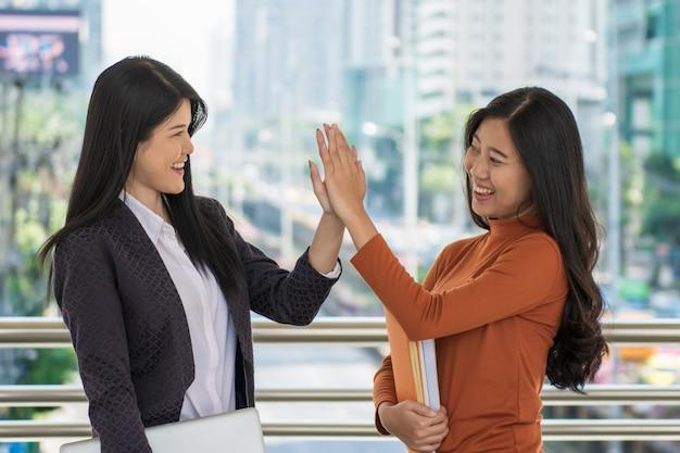 Junger glücklicher student, der bücher und klapshände oder hallo fünf am campus zusammenhält.