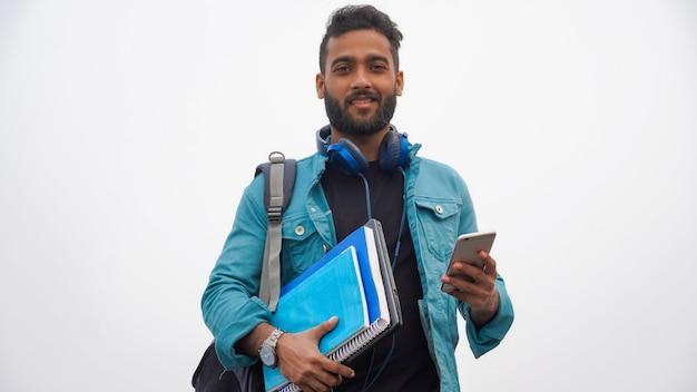 Junger glücklicher student mit büchern und laptop unter verwendung des handys