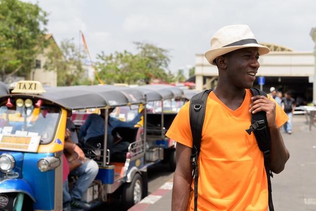 Junger glücklicher touristenmann, der beim denken und sightseeing am bahnhof in bangkok thailand lächelt