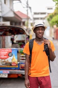Junger glücklicher touristenmann, der lächelt und denkt, während rucksack in den straßen von bangkok thailand hält