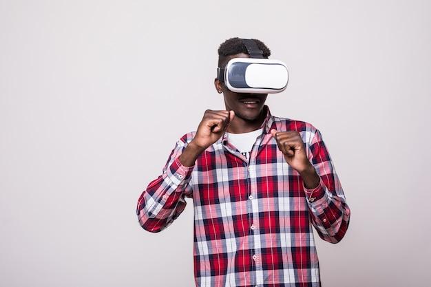 Junger glücklicher und aufgeregter afroamerikanischer mann, der vr schutzbrille der virtuellen realität trägt und videospiel genießt, das in innovation und spielbox isoliert wird