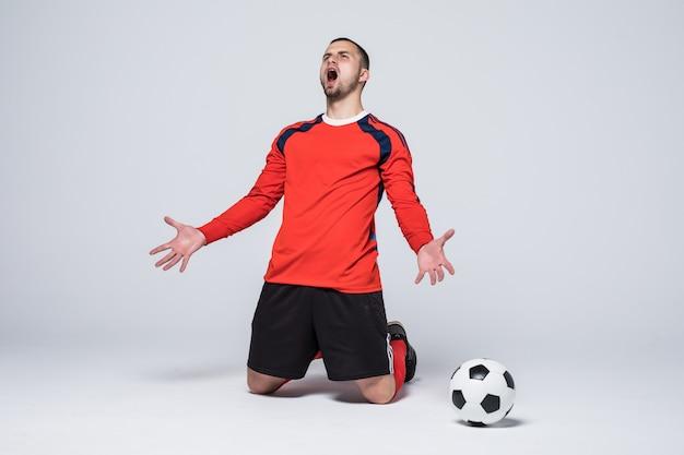Junger glücklicher und aufgeregter fußballspieler im roten trikot, der das erzielte tor feiert