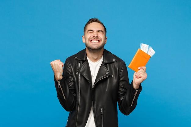 Junger glücklicher unrasierter mann in schwarzer jacke, weißem t-shirt, halten in der hand passtickets isoliert auf blauem wandhintergrund. passagier, der ins ausland reist. flugreisekonzept mock-up-kopienraum