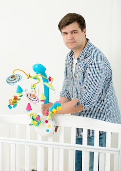 Junger glücklicher vater, der seinem kleinen sohn ein neues spielzeugkarussell im kinderbett zeigt