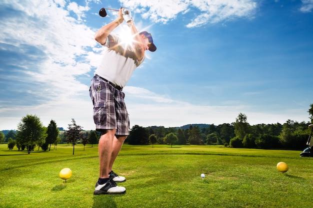 Junger golfspieler auf dem kurs, der golfschwingen tut