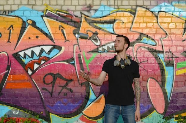 Junger graffiti-künstler mit gasmaske am hals werfen seine sprühdose gegen bunte rosa graffiti auf ziegelmauer. street art und zeitgenössischer malprozess