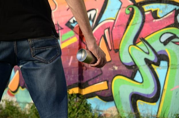 Junger graffiti-künstler mit rucksack und gasmaske an seinem hals malt bunte graffiti in den rosatönen auf ziegelwand. street art und zeitgenössischer malprozess