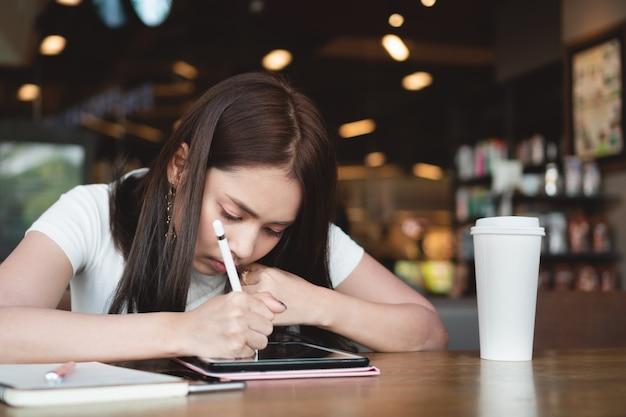 Junger grafikdesigner, der digitale tablette, notenstift und tasse kaffee auf holztisch am café verwendet.