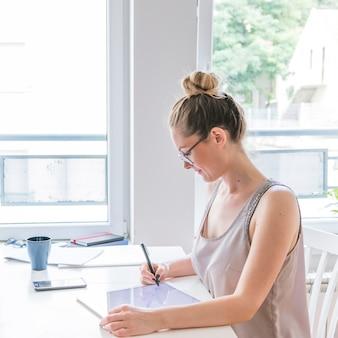 Junger grafikdesigner, der grafische digitale tablette am arbeitsplatz verwendet