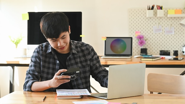 Junger grafikdesigner, der seine kamera und laptop im kreativen studio arbeitet.