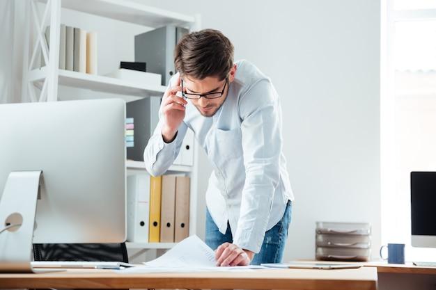 Junger gut aussehender geschäftsmann, der am schreibtisch steht und an dokumenten mit handy im büro arbeitet working