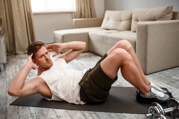 Junger gut gebauter mann gehen für sport in der wohnung. ernsthafter konzentrierter typ macht bauchmuskelübungen. er freut sich und hält die hände vom kopf weg. hart arbeitend.