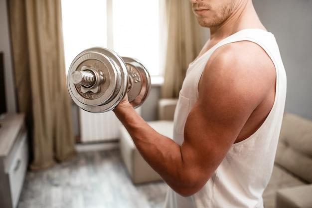 Junger gut gebauter mann streben herein sport in der wohnung an. schneiden sie die ansicht des kerls bizepsdummkopfübungen allein tuend. er schaut muskeln an. tageslicht.