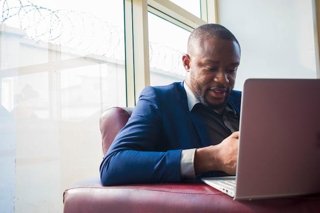 Junger gutaussehender afrikanischer geschäftsmann, der aufgeregt ist, was er auf seinem laptop tut