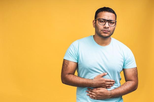 Junger gutaussehender afroamerikanischer schwarzer indischer mann mit hand auf dem bauch, weil verdauungsstörungen, schmerzhafte krankheit, die sich unwohl fühlt, isoliert auf gelbem hintergrund. konzept für bauchschmerzen.