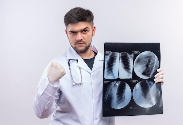 Junger gutaussehender arzt, der weiße medizinische handschuhe und stethoskop des weißen medizinischen kleides trägt und faust zeigt, die wütend tomographie hält, die über weißer wand steht