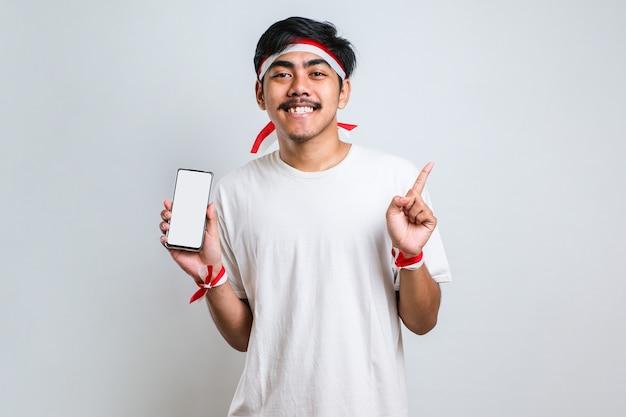 Junger gutaussehender asiatischer mann, der bildschirm des smartphones auf weißem, isoliertem hintergrund zeigt, sehr glücklich mit hand und finger zur seite zeigend