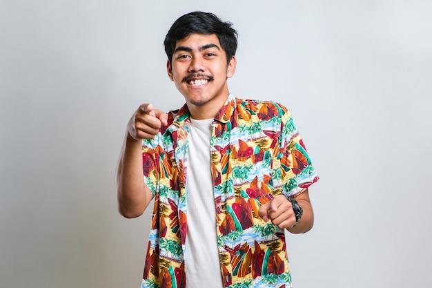 Junger gutaussehender asiatischer mann, der ein lässiges hemd trägt, das auf rotem hintergrund steht und mit den fingern auf sie und die kamera zeigt, positiv und fröhlich lächelt