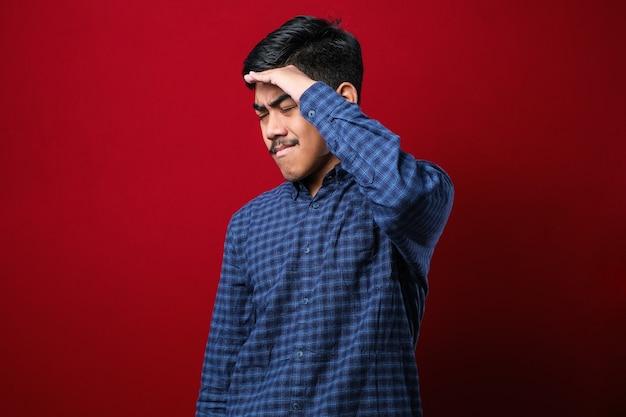 Junger, gutaussehender asiatischer mann, der ein lässiges hemd trägt, das über isoliertem rotem hintergrund mit der hand auf dem kopf für schmerzen im kopf steht, weil stress migräne leiden.