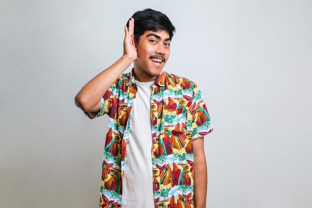 Junger gutaussehender asiatischer mann, der ein lässiges hemd trägt, das über isoliertem weißem hintergrund steht und mit der hand über dem ohr lächelt und eine anhörung zu gerüchten oder klatsch hört. taubheitskonzept.