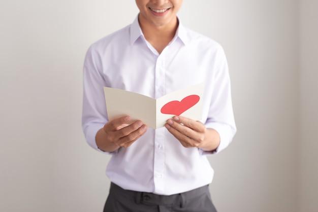 Junger gutaussehender asiatischer mann liest grußkarte mit herzform auf weißem hintergrund