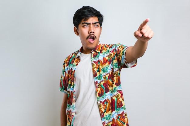 Junger gutaussehender asiatischer mann mit freizeithemd, der auf weißem hintergrund steht und mit dem finger überrascht nach vorne zeigt, offener mund erstaunter ausdruck, etwas auf der vorderseite